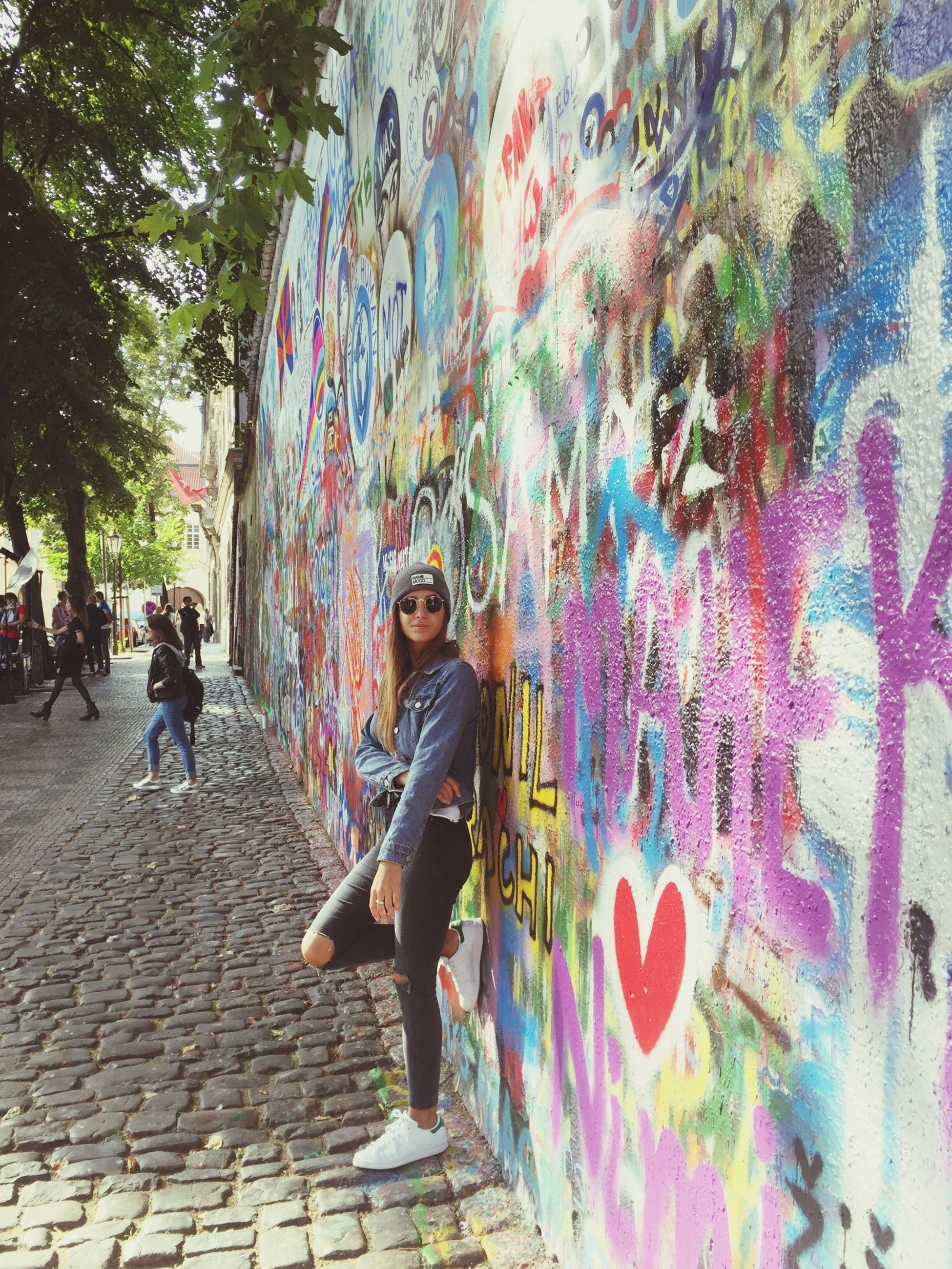 art, graffiti, creativity, art and craft, multi colored, wall - building feature, street art, built structure, architecture, full length, tree, vandalism, painting, building exterior, person, day, colorful, city life, outdoors, footpath, artwork