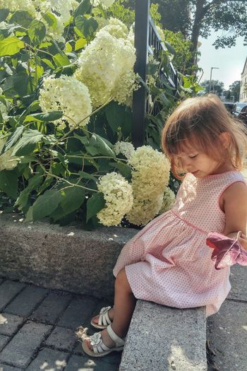 Young girl sitting near flowers. Childhood Day Outdoors Real People Lifestyles Girls Children Only Nature One Person Relaxing Flowers In Bloom Flower Collection Plants Flower Polkadots