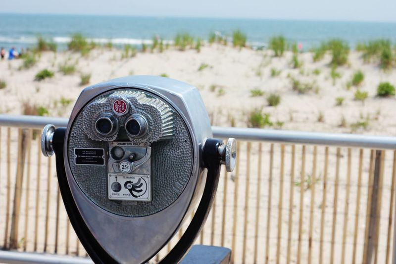 Coin operated binoculars with a sand dune background EyeEm Selects Binoculars Coin Operated Coin-operated Binoculars Day Close-up Focus On Foreground Railing Nature Sky No People Security Sunlight Metal Surveillance Outdoors Water Sea Fence Observation Point Barrier