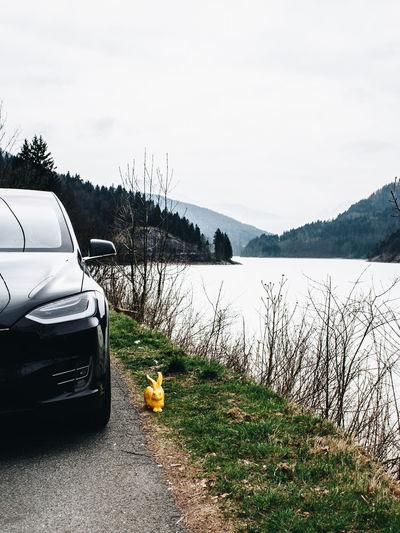 Car by lake against sky