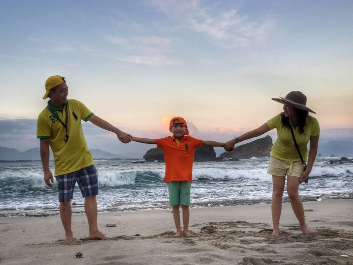 Portrait of boy enjoying with parents at beach against sky during sunset