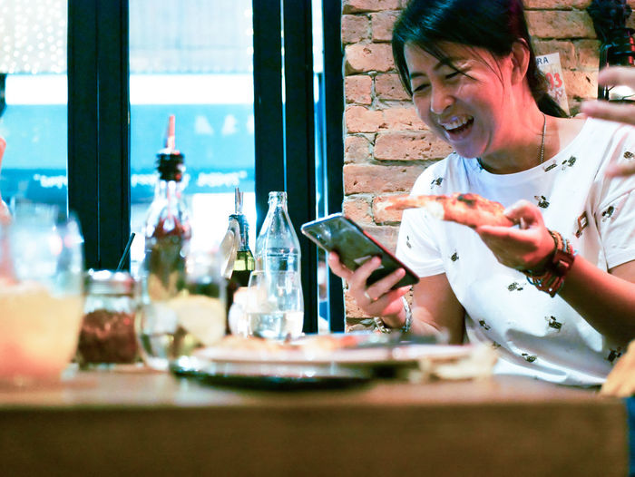 Cheerful woman using phone while having pizza at table in restaurant