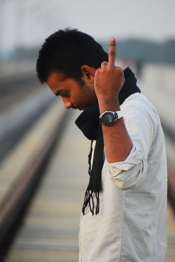 Side view of man showing middle finger