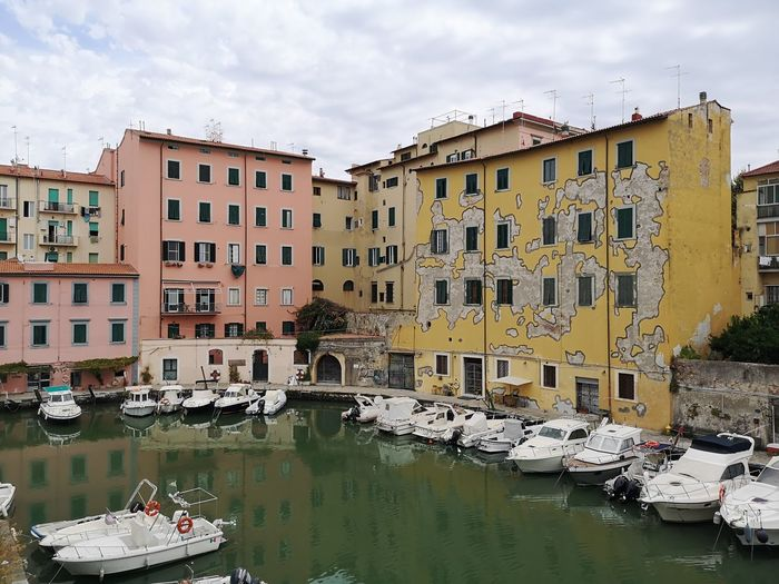 Boats moored in canal by buildings against sky
