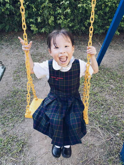 Portrait of smiling girl sitting on swing in playground