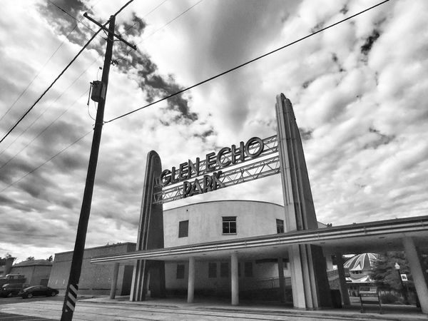 Low Angle View Cable Transportation Architecture Cloud - Sky Power Line  Cloudy Street Sky Built Structure Man Made Object Sign Monochrome Black & White IPhoneography Glen Echo Park Pole Cloud Public Transport Building Exterior Day Outdoors Railroad Station Power Cable Tall - High