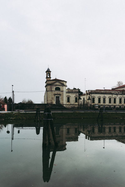Little church reflection on the riverside in Dolo Italy Church Riverside Architecture Bell Tower Building Exterior Built Structure Clear Sky Day Desaturated History Instagram Instagram Look Nature No People Outdoors Puddle Reflection River Sky Street Streetphotography Travel Destinations Tree Water