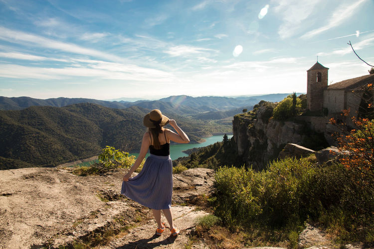 Rear view of woman standing at siurana against sky
