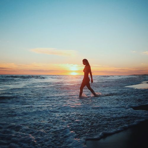 Woman wearing bikini while walking in sea against sky during sunset