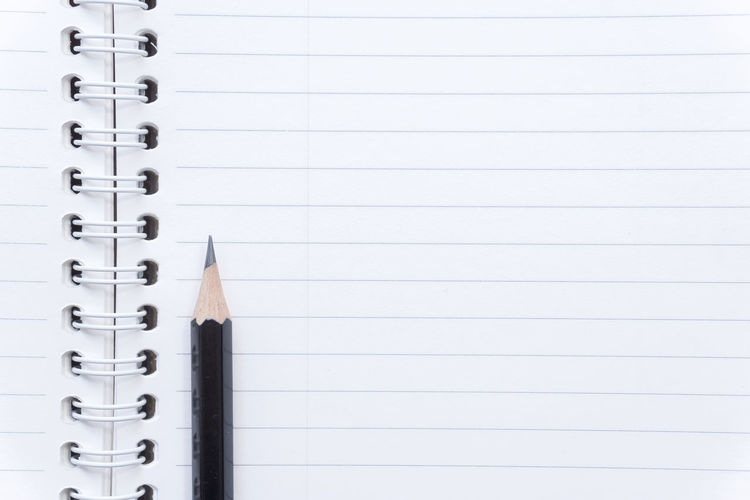Full frame shot of open blank spiral notebook and pencil