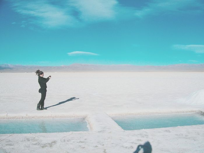 Woman standing on salt pan against sky