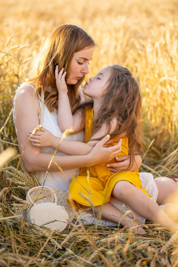 Mother and daughter embracing while sitting on field