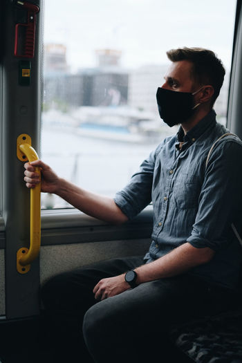 Close-up of mid adult man wearing mask sitting in bus
