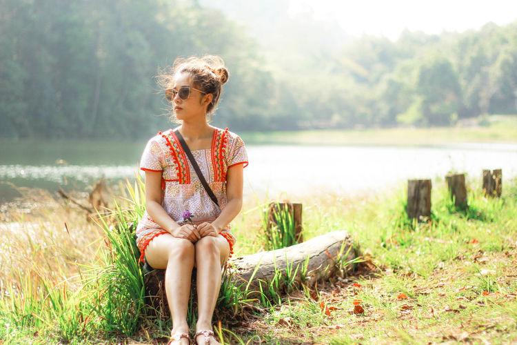 Woman sitting on log against lake