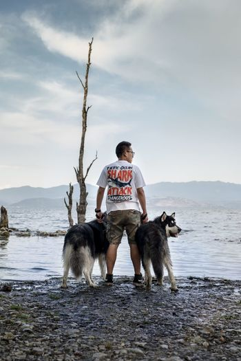 Young man with dog sitting on beach