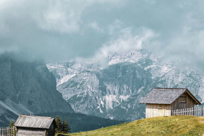 Log Cabins By Snowcapped Mountains Against Cloudy Sky