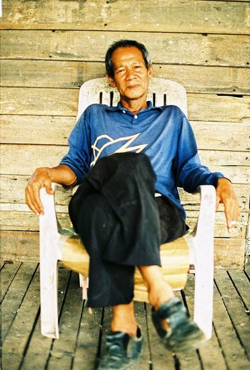 men at houseboat and capture with film camera EyeEmNewHere Adult Casual Clothing Chair Contemplation Day Front View Full Length Leisure Activity Males  Men One Person Portrait Real People Relaxation Seat Senior Adult Senior Men Sitting Walking Cane Wood - Material
