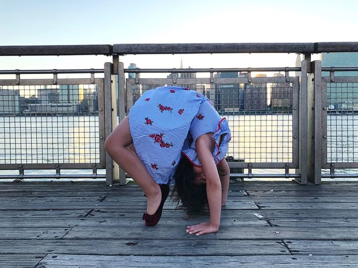 Side view of girl bending backwards on pier by river against clear sky in city during sunset