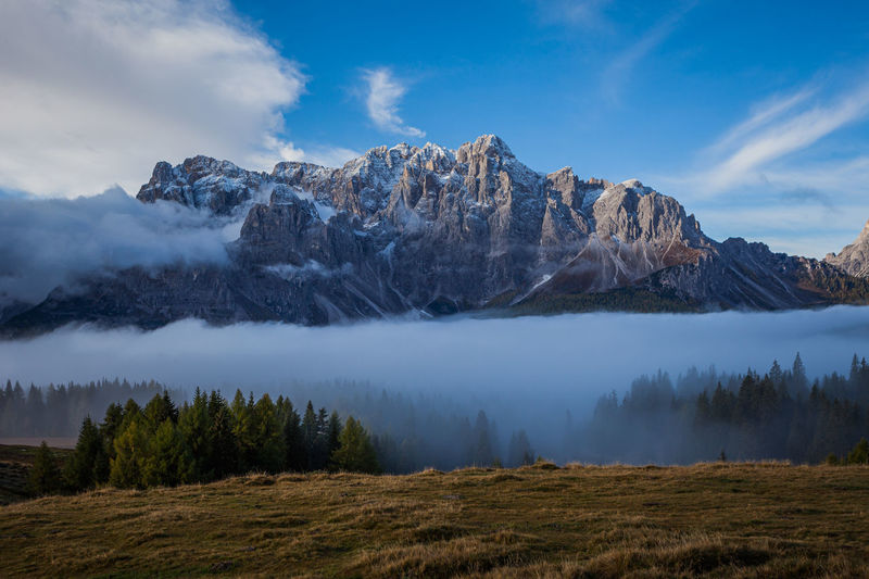 Clouds and fog at dawn from which the wonderful peaks of the dolomites of sesto spring up, italy