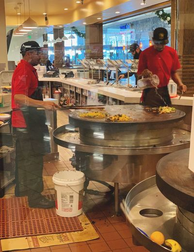 """The Wok Cookers"" Two cooks prepare Mongolian BBQ dishes at an open cooking center behind a glass partition, where patrons can watch their customized dishes being prepared, at a mall in Northern California. Restaurants Mongolian Bbq Chefs Cooks Wok Men Occupation Food And Drink Adult Food Business Retail  Indoors  People Working"