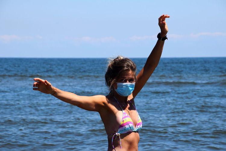 Woman with arms raised on beach against sky