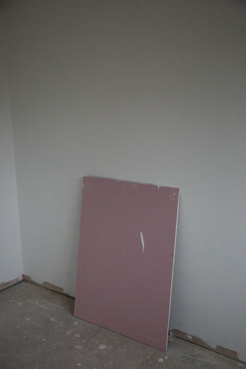 Empty chair against white wall of house