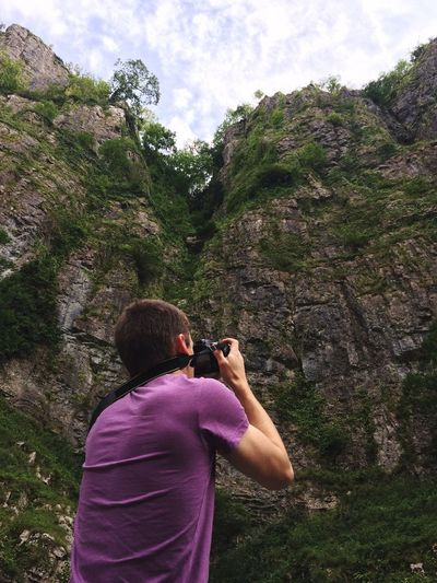 Rear view of man photographing at cheddar gorge