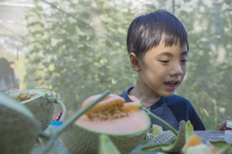 Close-Up Of Boy Standing By Muskmelons