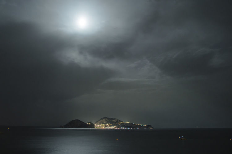 Island Amidst Sea Against Cloudy Sky At Night