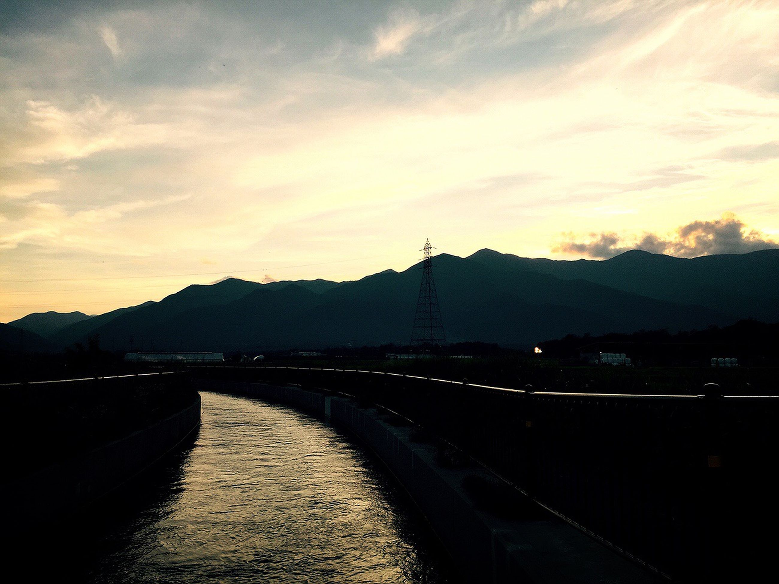 mountain, water, sky, sunset, mountain range, transportation, river, connection, bridge - man made structure, tranquility, tranquil scene, built structure, scenics, the way forward, cloud - sky, beauty in nature, road, dusk, nature, architecture