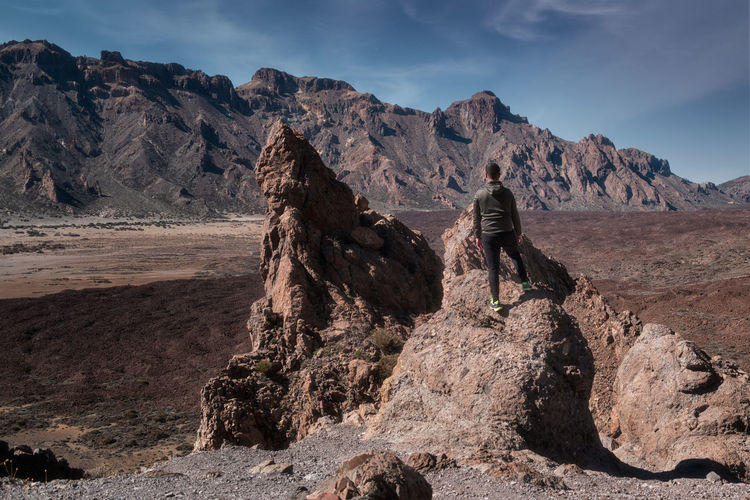 Rear view of man on rock in mountains against sky