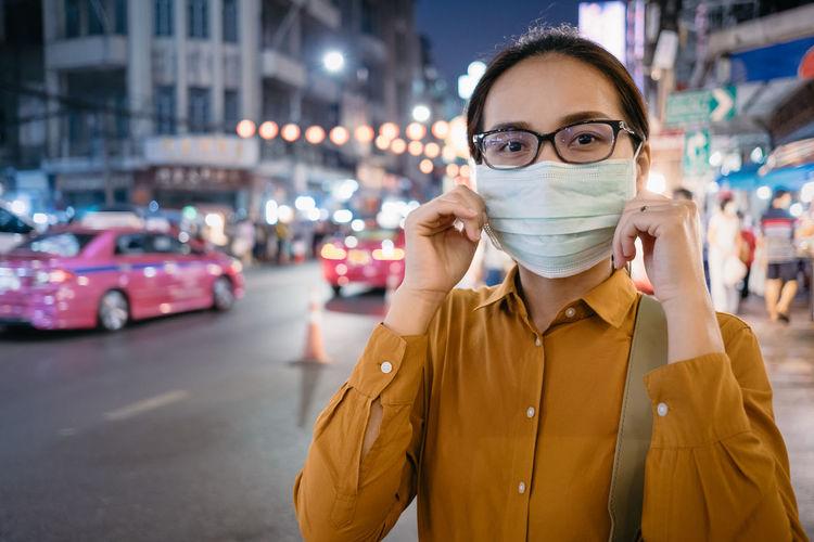 Portrait of woman wearing mask standing on street in city