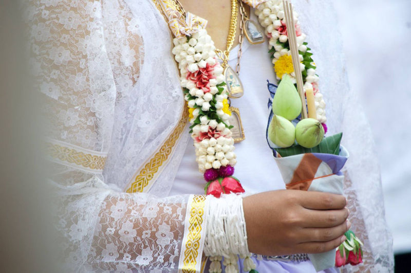 Midsection of bride wearing floral garland