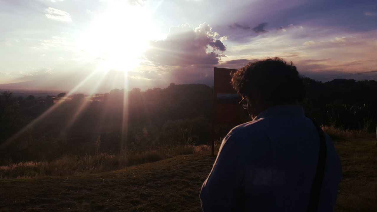 rear view, sunset, sun, real people, sunbeam, lens flare, sunlight, one person, waist up, sky, nature, leisure activity, tree, lifestyles, outdoors, women, standing, photographing, technology, photography themes, men, beauty in nature, scenics, day, people