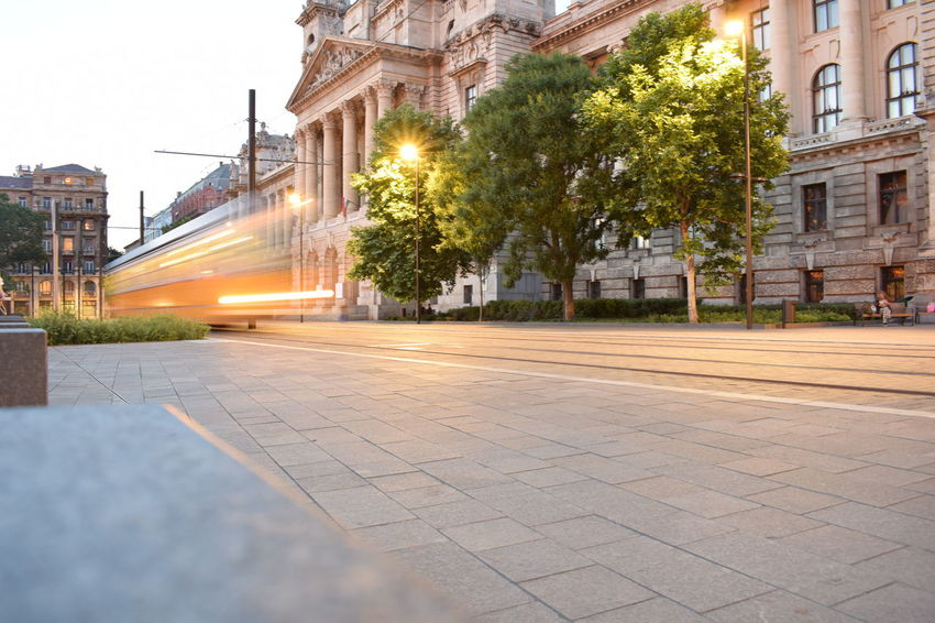 Budapest Hungary Tram Architecture Building Building Exterior Built Structure City City Life Day Empty Footpath Illuminated Longexposure Longexposurephotography Nature No People Outdoors Paving Stone Residential District Sky Street Travel Destinations Tree