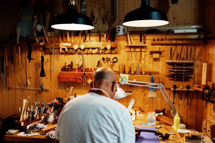 Man working at illuminated shop