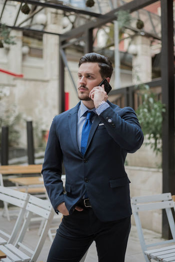 Businessman talking on mobile phone while standing in city