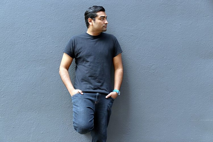 Cool young handsome man standing against a grey wall American Black Casual Clothing College Cool Day Gray Grey Hairstyle Handsome Indian Jeans Model One Person Outdoors Portrait Pose Serious Smart Standing Student Tech Technology Watch Young Adult