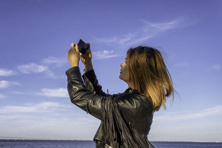 Side view of woman taking selfie standing against selfie