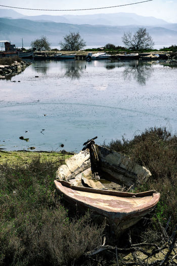 A boat rotting on land at the small harbour of Kopraina, in western Greece. The decay of the harbour is denoted though the decay of the boat Boat Day Grass Greece Nature Nautical Vessel No People Outdoors Sky Tree Water