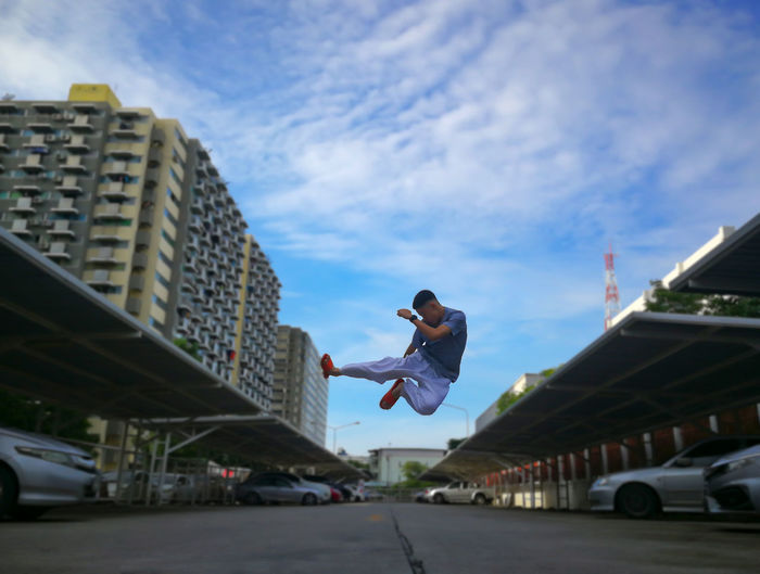 Boy jumping on road in city against sky