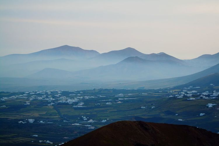 Scenic view of misty landscape and mountains against sky at lanzarote