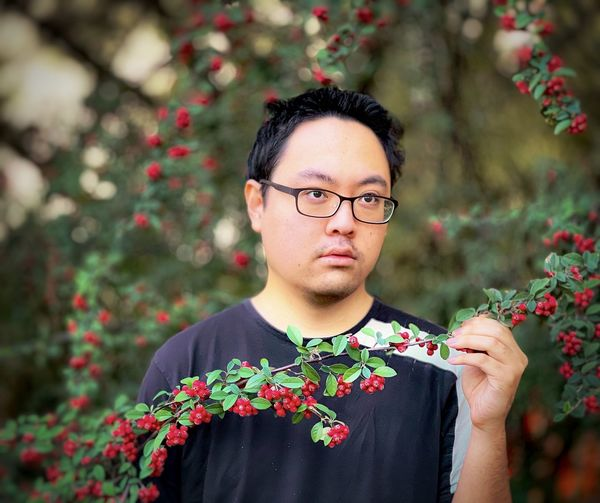 Portrait of young man wearing eyeglasses and holding red rowan berries branch against rowan tree.