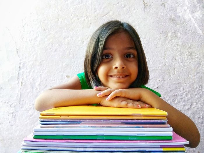 portrait of smiling little girl with books Girl Kid Looking At Camera Indian Culture  Smiling Young Girl Window Light Confidence  Happiness Education Close-up Cuteness Asian  Indian Child Childhood Facial Expression Portrait Textbook Workbook Homework School Supplies Book Back To School