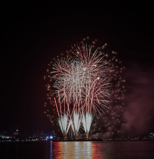 Sea in front of firework display at night