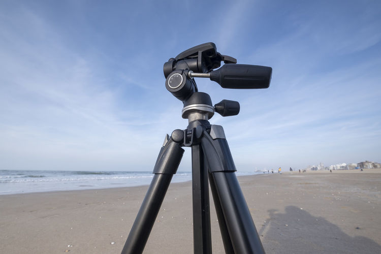 Low angle view of tripod on beach against sky