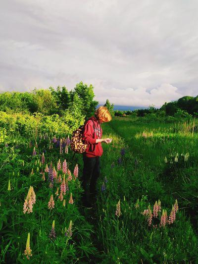 Boy standing on grassy land against sky
