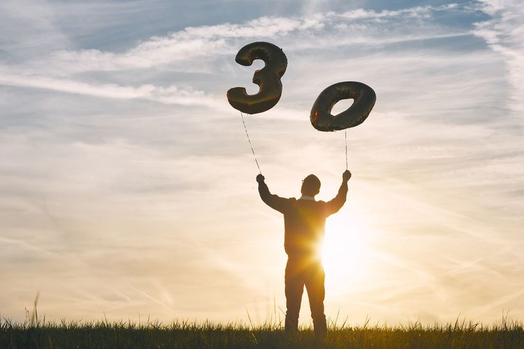 Low angle view of man holding number 30 helium balloons against sky