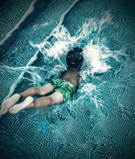 High angle view of boy diving into swimming pool