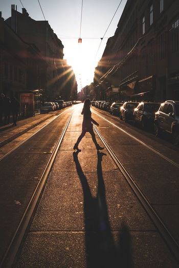 Woman walking on road in city during sunny day